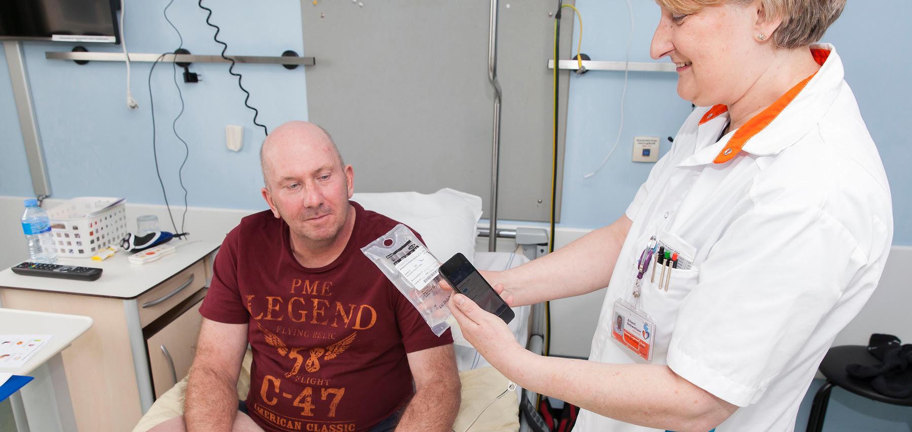 De verpleegkundige scant met de iPod de infuuszak en de barcode op het polsbandje van de patiënt