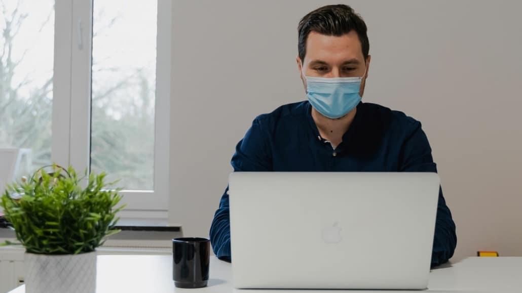 Man met mondkapje achter laptop
